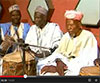 Group of men with traditional instruments, still from video
